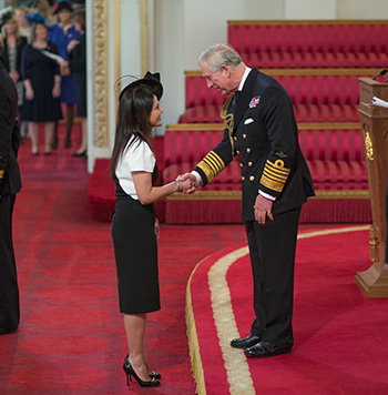 Kavita receiving her OBE from Prince Charles